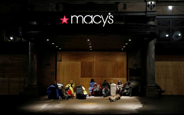 Homeless people sleep under the awning of Macy's boarded up Herald Square store, as protesters rally against the death in Minneapolis police custody of George Floyd, in New York City, New York, US, June 3, 2020. Reuters