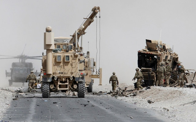 US troops assess the damage to an armoured vehicle of NATO-led military coalition after a suicide attack in Kandahar province Afghanistan