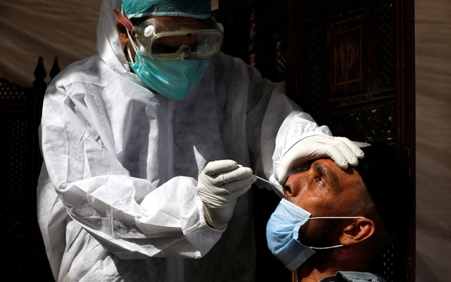 A paramedic wearing protective gear takes a nose-swab sample to be tested for the coronavirus disease (COVID-19), in Karachi, Pakistan June 27, 2020. REUTERS