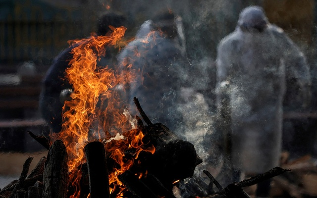 A burning pyre of a man who died due to the coronavirus disease (COVID-19), is seen as another one is carried for cremation at a crematorium in New Delhi, India, June 3, 2020. REUTERS