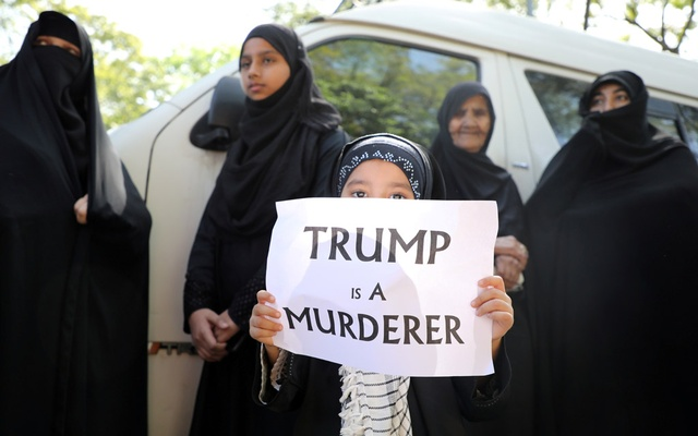 """A girl holds a sign reading """"Trump is a murderer"""" during a condolence ceremony for Iranian Major-General Qassem Soleimani, who was killed in a airstrike near Baghdad, outside the Embassy of Iran in Kuala Lumpur, Malaysia, Jan 7, 2020. REUTERS/FILE"""