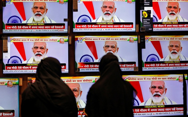 Women watch Indian Prime Minister Narendra Modi address the nation amid the spread of the coronavirus disease (COVID-19), on TV screens inside a showroom in Ahmedabad, India, Jun 30, 2020. REUTERS