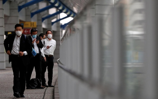 Businessmen wearing protective face masks are seen on a pedestrian bridge, amid the spread of the coronavirus disease (COVID-19), in a business district in Tokyo, Japan June 24, 2020. REUTERS