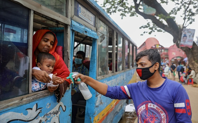 A man sprays hand sanitizer to a child who is travelling on a public bus amid the coronavirus disease outbreak in Dhaka on Jun 22. REUTERS