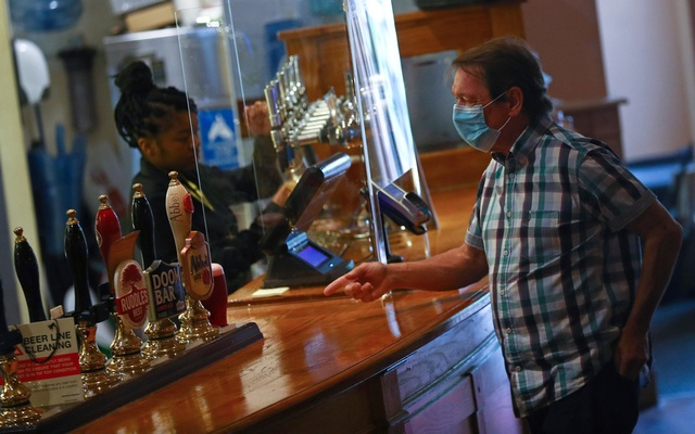 A customer is seen at a bar at The Holland Tringham Wetherspoons pub after it reopened following the outbreak of the coronavirus disease (COVID-19), in London, Britain July 4, 2020. Reuters