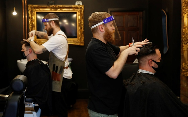 Customers wearing face masks get their hair cut at a barber shop after its reopening following the outbreak of the coronavirus disease (COVID-19), in Altrincham, Britain July 4, 2020. Reuters