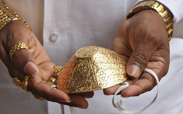 Shankar Kurhade shows his face mask made out of gold as he poses for a photograph amidst the spread of the coronavirus disease (COVID-19) in Pune, India, July 4, 2020. Reuters