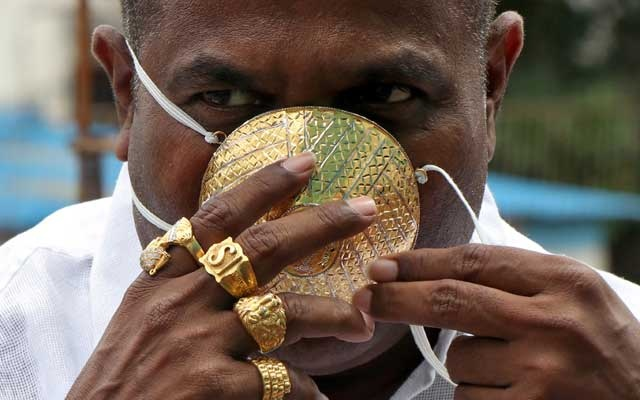 Shankar Kurhade (48), wears his face mask made out of gold as he poses for a photograph amidst the spread of the coronavirus disease (COVID-19) in Pune, India, Jul 4, 2020. Kurhade claims the mask weighs 50 grams and costs around $3870. REUTERS