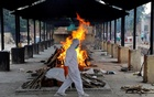 A priest wearing personal protective equipment (PPE) walks in front of the body of a person who died of the coronavirus disease (COVID-19), as he collects woods to make a funeral pyre at a crematorium in New Delhi, India, July 3, 2020. REUTERS/Anushree Fadnavis