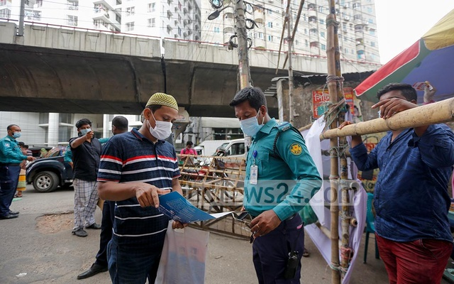 A man shows a doctor's prescription to a police official as an explanation that he went out to buy drugs in a locked-down area of Dhaka's Wari. Photo: Mahmud Zaman Ovi