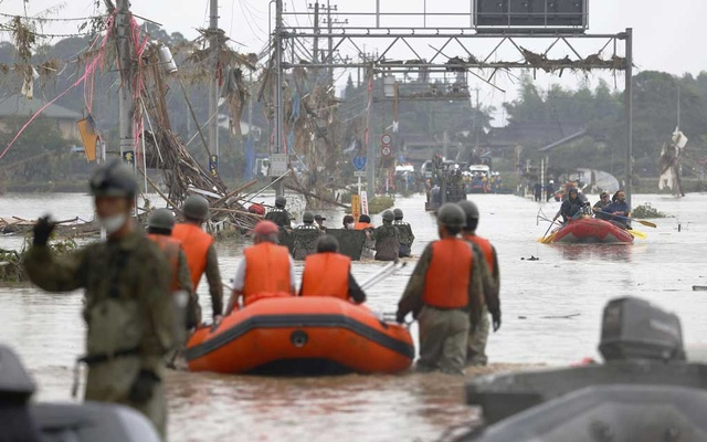 Local residents are rescued by Japanese Self-Defence Force soldiers using a boat at a flooding area caused by a heavy rain in Kuma village, Kumamoto prefecture, southern Japan, in this photo taken by Kyodo July 5, 2020. Kyodo/via REUTERS