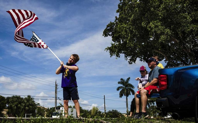 Andrew Buckley waves an American flag alongside his family while they wait for a Fourth of July parade of city employees and government officials in Margate, Fla., on Saturday, amid the coronavirus pandemic. THE NEW YORK TIMES