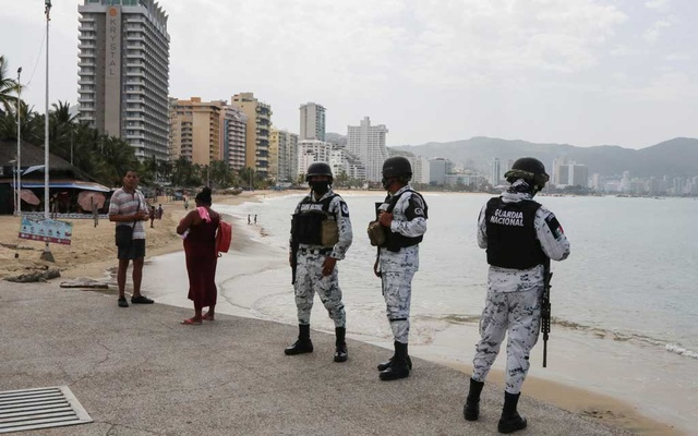 Members of Mexico's National Guard keep watch during the reopening of the beaches and hotels after confinement measures were eased this week, as the coronavirus disease (COVID-19) outbreak continues in Acapulco, Mexico July 2, 2020. REUTERS