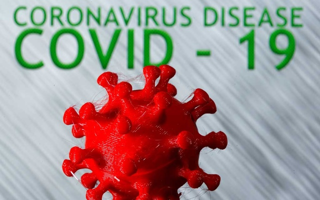 A 3D-printed coronavirus model is seen in front of the words coronavirus disease (Covid-19) on display in this illustration. REUTERS