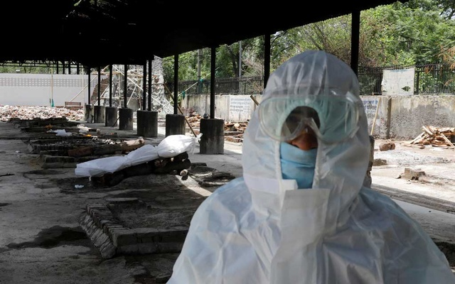 A relative in personal protective equipment stands next to the body of a man who died due to the coronavirus disease, at a crematorium in New Delhi on Jul 5. REUTERS