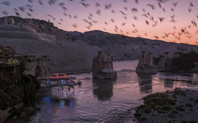 Birds fly over the Tigris River near Hasankeyf, Turkey, Nov 3, 2019. In his push for economic development, Turkey's president has flooded the archaeological gem of Hasankeyf and displaced thousands of families. Mauricio Lima/The New York Times