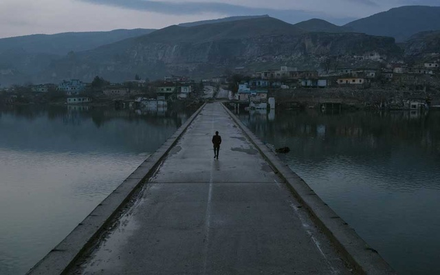 A resident walks across a bridge to the old town of Hasankeyf, Turkey, partially submerged by the Tigris River, Feb 20, 2020. Mauricio Lima/The New York Times