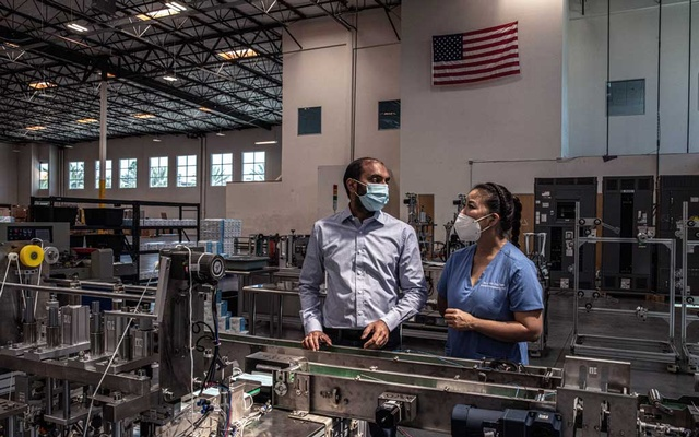 The chief executive of QYK Brands, Rakesh Tammabattula, with his wife, Dr. Jacqueline Nguyen, on the factory floor in Anaheim, Calif., on May 20, 2020. When it shifted to making medical masks in response to the coronavirus pandemic this year, QYK Brands had to import the fabric-cutting machines from China. (Bryan Denton/The New York Times)