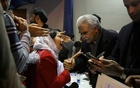 Pakistan's Health Minister, Zafar Mirza (R), interacts with the mother of a Pakistani student, who is stuck in the locked down Hubei province at the center of China's coronavirus outbreak, as people demand evacuation of their children during a meeting in Islamabad, Pakistan February 19, 2020. REUTERS