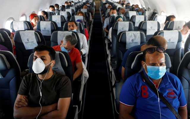 Passengers wearing protective face masks sit on a plane at Sharm el-Sheikh International Airport, following the outbreak of the coronavirus disease (COVID-19), in Sharm el-Sheikh, Egypt, Jun 20, 2020. REUTERS