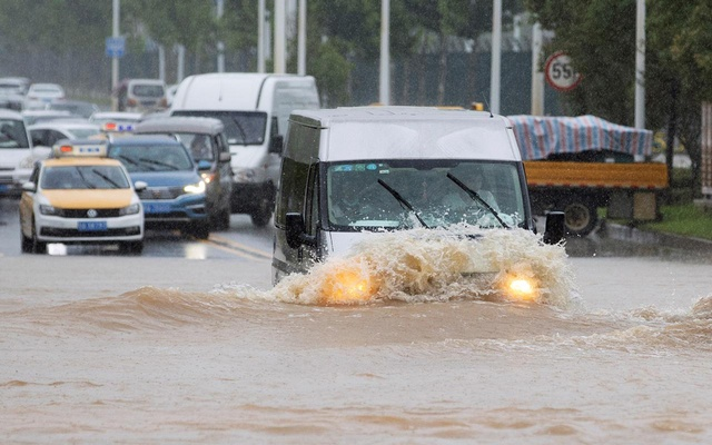 A vehicle travels through a flooded section of a road following heavy rainfall in Wuhan, Hubei province, China July 6, 2020. China Daily via REUTERS