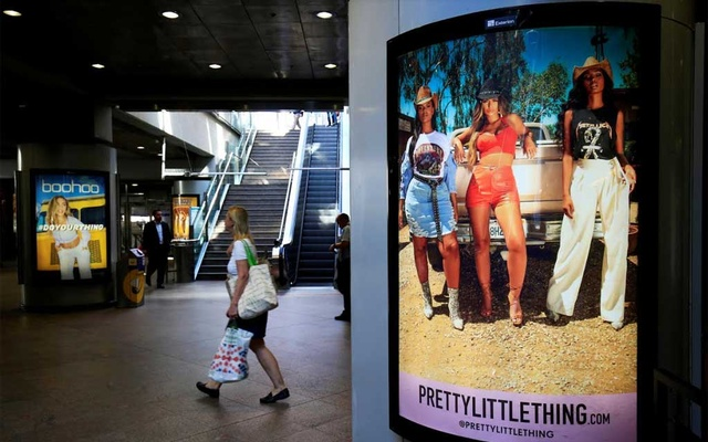 A shopper walks pass advertising billboards for Boohoo and for 'Pretty Little Things', a Boohoo brand, at Canary Wharf DLR station in central London, Britain, Sept 17, 2018. REUTERS
