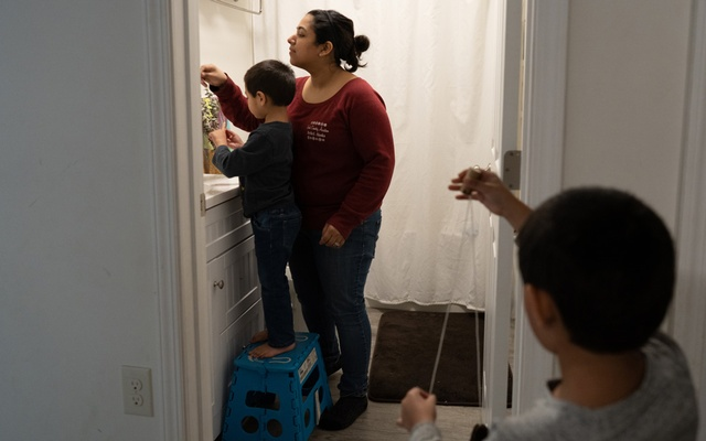 Rebecca Trimble, with her boys Elliot, 5, and Jay, 4, helps the youngest get ready to brush his teeth, in Bethel, Alaska, March 8, 2020. (Ash Adams/The New York Times)