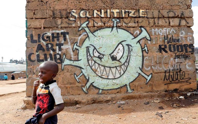 A boy stands in front of a graffiti promoting the fight against the coronavirus disease (COVID-19) in the Mathare slums of Nairobi, Kenya, May 22, 2020. REUTERS
