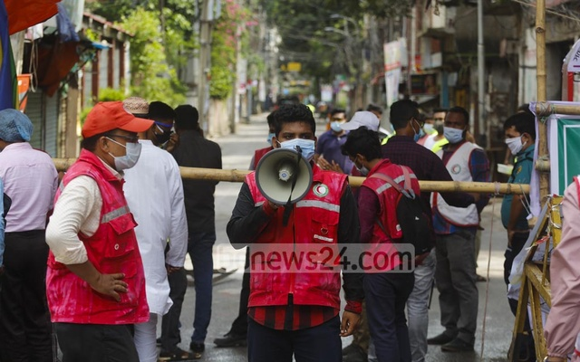 A volunteer urging residents not to crowd by using a loudhailer at an end of Chandicharan Bose Street, the only point for entry into or exit from several coronavirus hotspots locked down in Dhaka's Wari. Photo: Mahmud Zaman Ovi