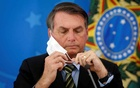 Brazil's President Jair Bolsonaro adjusts his protective face mask during a press statement to announce federal judiciary measures to curb the spread of the coronavirus disease (COVID-19) in Brasilia, Brazil March 18, 2020. REUTERS