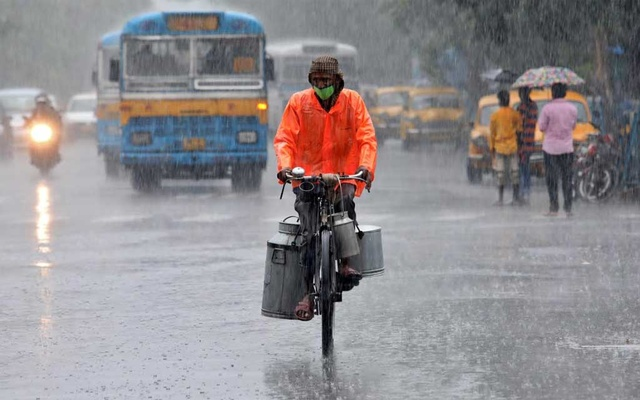 A milk vendor wearing a protective face mask rides his bicycle during heavy rain, after authorities eased lockdown restrictions that were imposed to slow the spread of the coronavirus disease (COVID-19), in Kolkata, India, June 12, 2020. REUTERS