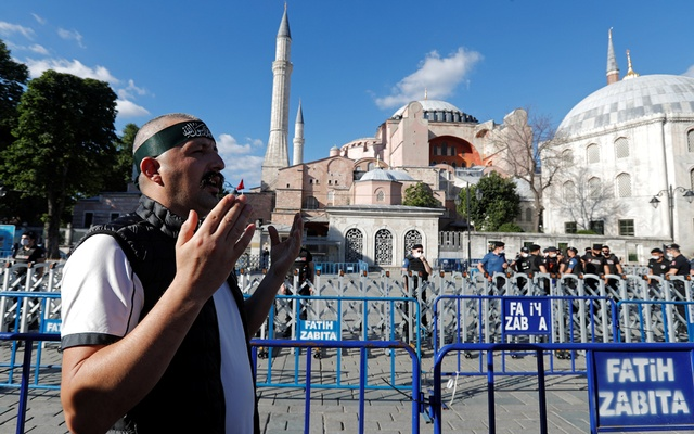 A Muslim man prays in front of the Hagia Sophia or Ayasofya, after a court decision that paves the way for it to be converted from a museum back into a mosque, in Istanbul, Turkey, July 10, 2020. Reuters