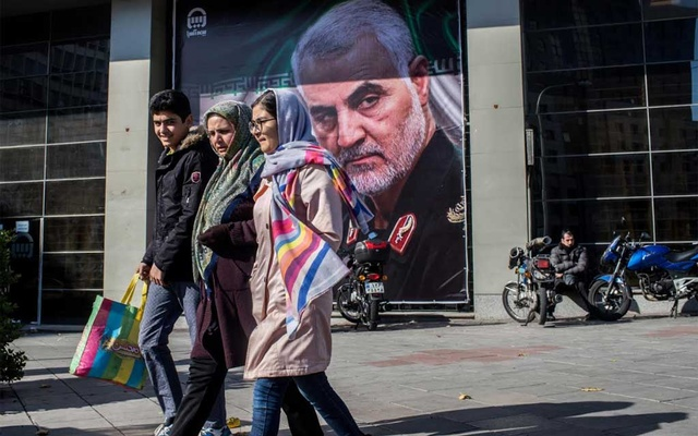 People pass a banner of Iranian Major Gen Qasem Soleimani, who was killed by an American drone strike, in Tehran, Iran, Jan 5, 2020