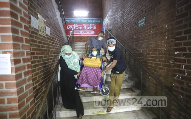 Relatives taking Jahanara Begum, who is undergoing treatment at the COVID-19 isolation ward of Shaheed Suhrawardy Medical College and Hospital in Dhaka, for an electrocardiogram (ECG) test. Photo: Asif Mahmud Ove