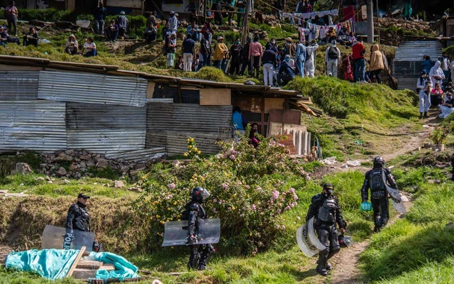 Police officers evict residents of an illegal settlement in Bogota, Colombia, May 11, 2020. The New York Times