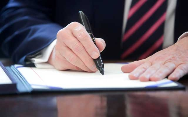 President Donald Trump signs the Paycheck Protection Program and Health Care Enhancement Act financial response to the coronavirus disease (COVID-19) outbreak, in the Oval Office at the White House in Washington, US April 24, 2020. REUTERS