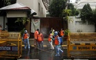 Municipal workers in personal protective equipment (PPE) wait to enter the residence of Bollywood actor Amitabh Bachchan to sanitise it after he and his son, actor Abhishek Bachchan, tested positive for the coronavirus disease (CIVID-19), in Mumbai, India, Jul 12, 2020. REUTERS