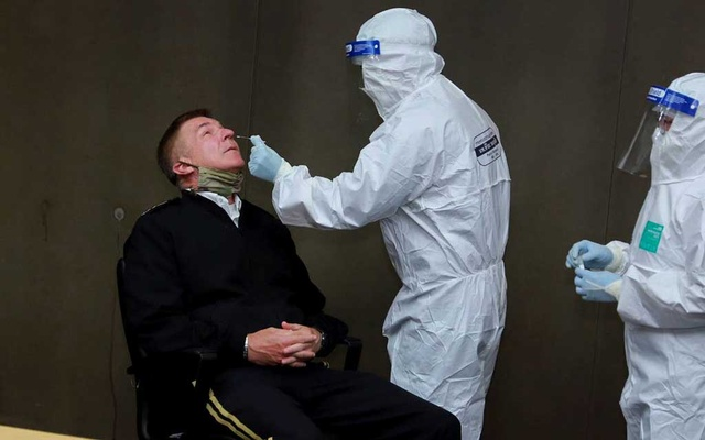 A health officer wearing personal protective equipment performs a nose swab test on US Army Chief of Staff General James C McConville at a military airport in Bangkok on Jul 9. REUTERS