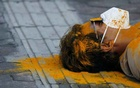 A protester covered in turmeric powder protests by lying down on the sidewalk of a street during a demonstration demanding a more effective government response to the coronavirus disease (COVID-19) outbreak, in Kathmandu, Nepal, Jun 20, 2020. REUTERS