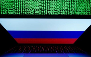 A Russian flag is seen on the laptop screen in front of a computer screen on which cyber code is displayed, in this illustration picture taken March 2, 2018. REUTERS