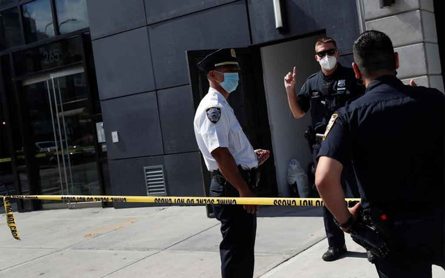 NYPD officers speak at crime scene at 265 Houston Street, where Fahim Saleh, Co-founder/CEO of Gokada, was found dead at the apartment building in New York City, New York, US, July 15, 2020. Reuters
