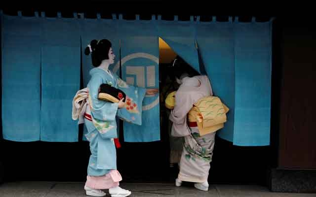 Koiku and Mayu, who are geisha, enter Asada, a luxury Japanese restaurant where their customers are hosting a party, which they will be entertaining with other geisha, during the coronavirus disease outbreak, in Tokyo.