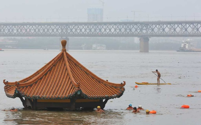 People swim near a pavilion partially submerged in floodwaters on the banks of the Yangtze River, following heavy rainfall in Wuhan, Hubei province, China Jul 8, 2020. REUTERS