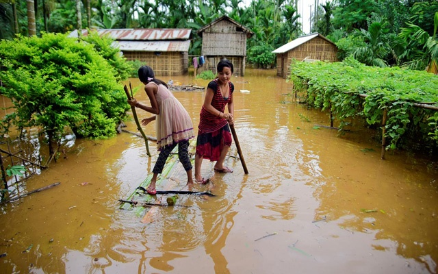 Girls row a makeshift raft past submerged houses at a flood-affected village in Karbi Anglong district, in the northeastern state of Assam, India, July 11, 2019. REUTERS