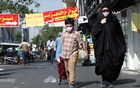 An Iranian woman and her son wearing a protective face mask walks the street, following the outbreak of the coronavirus disease (COVID-19), in Tehran, Iran, June 28, 2020. REUTERS