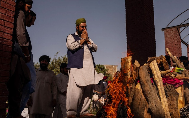 FILE -- Members of the Afghan Sikh community mourn as bodies of people killed in a suicide bombing are cremated in Kabul, Afghanistan, July 2, 2018. The Indian government has said that it will expedite visas and the possibility of long term residency for Hindus and Sikhs who have been the target of bloody attacks in recent years amid Afghanistan's raging war. (Jim Huylebroek/The New York Times)