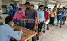 Bangladeshi expatriate workers wait in a queue to give their samples for COVID-19 tests at a temporary isolation centre installed in Mohakhali's DNCC market. The centre began collecting samples under the supervision of Dhaka district's civil surgeon on Monday. Photo: Asif Mahmud Ove