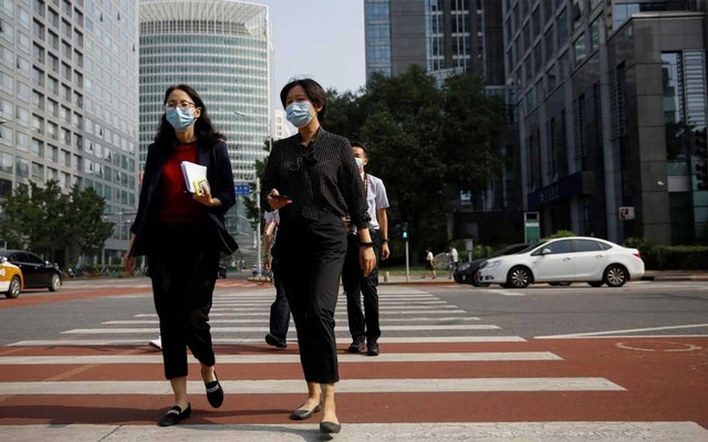 People wearing face masks following the outbreak of the coronavirus disease walk across a street in Beijing on Jul 16. REUTERS