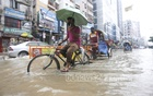 A man cycling while holding an umbrella on submerged Green Road in Dhaka on Tuesday. Photo: Asif Mahmud Ove
