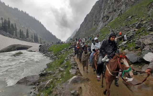Hindu pilgrims travel, either on ponies or on foot, along a track besides a glacier-fed stream during their annual pilgrimage to holy cave of Lord Shiva, in Pishutop, 114 km (71 miles) southeast of Srinagar Jun 25, 2012. REUTERS/FILE